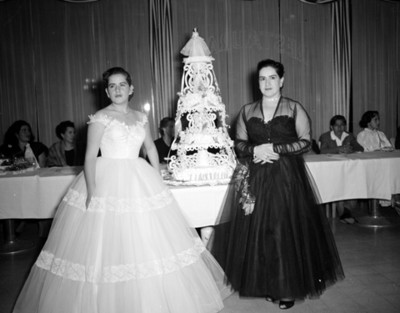 Quinceañera y mujer de pie junto a pastel
