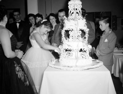 Quinceañera parte su pastel durante fiesta