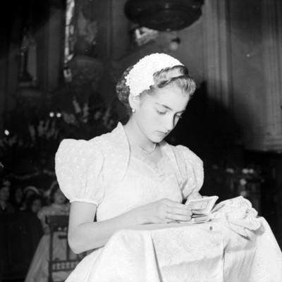 Mujer lee libro en el reclinatorio de una iglesia