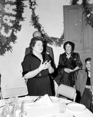 Mujer pronuncia discurso durante fiesta en un salón