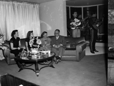 Mujeres sentadas en un sillón junto a un hombre con bebida