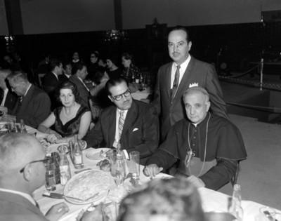 Sacerdote y empresarios durante banquete en el taller de una agencia automotríz