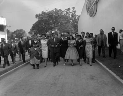 Adolfo López Mateos acompañado de mujeres y comitiva camina por una calle