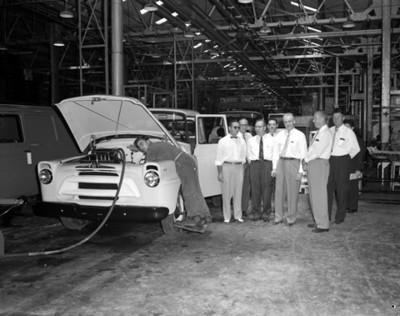 Empresarios junto a un automóvil en instalación industrial, interior