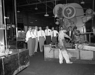 Empresarios observan a obrero operar una máquina en instalación industrial