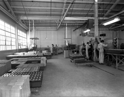 Hombres trabajan en una fábrica de baterias automotríces