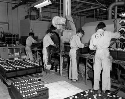 Hombres colocan tapas a baterias automotrices durante fabricación