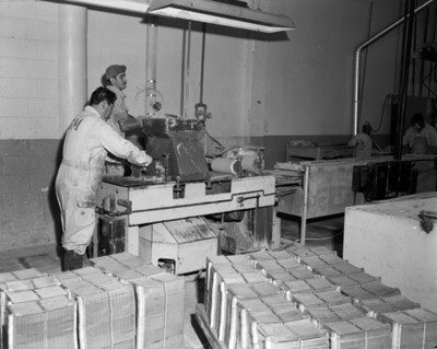 Hombres operan maquinaria durante fabricación de baterías automotrices