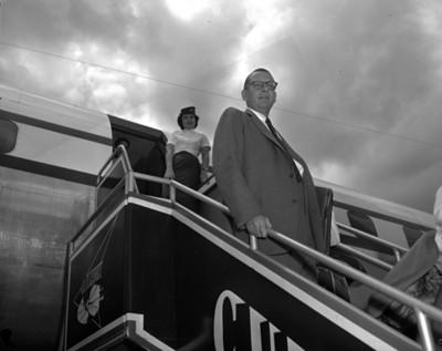Empresarios y azafata en las escaleras de un avión, retrato