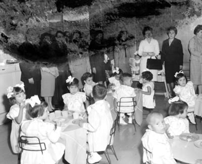 Eva Samano de López Mateos y mujeres observan a niños en comedor de INPI