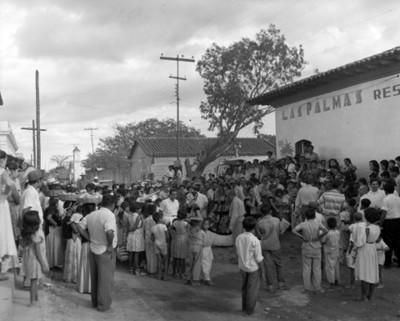 Gente observa un baile regional enfrente de restaurante las Palmas