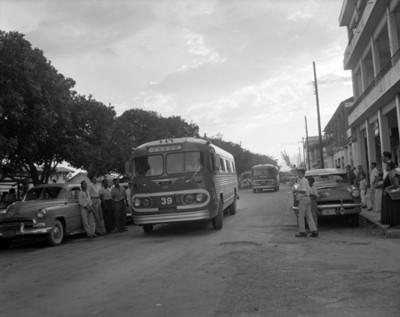 Autobús pasa junto a hombres recargadas en autobús