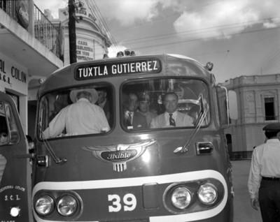Hombres abordo de un autobús con la puerta abierta