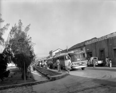 Autobuses estacionados frente al parque de un poblado