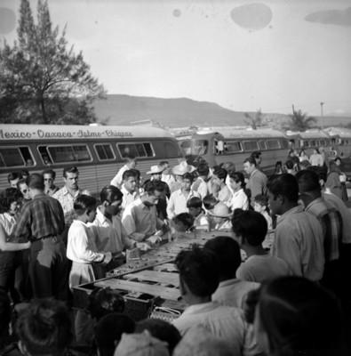 Gente observa a músicos en la caolle de un poblado