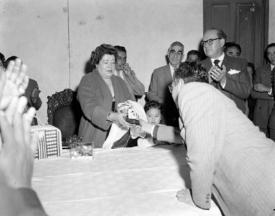 Hombre entrega obsequio a mujer durante reunión con empresarios