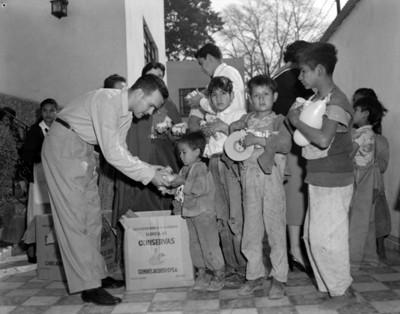Niños reciben de un hombre latas de avena