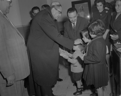 Sacerdoate toca frente de un niño durante ceremonia religiosa