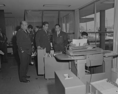 Militares y ejecutivo observan a empleado en una oficina