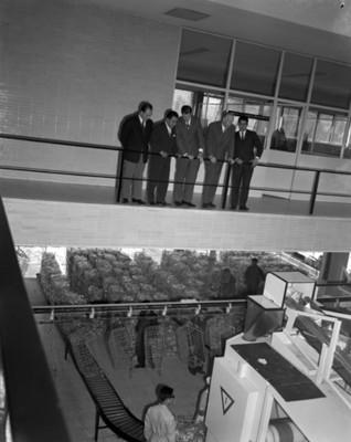 Hombres observan praoacaeso en una fábrica