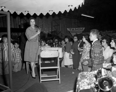 Mujer con un microfono junto a una máquina de coser