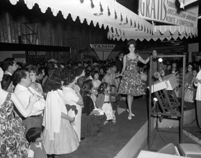 Mujer con su mano sobre una vitrina con una máquina de coser