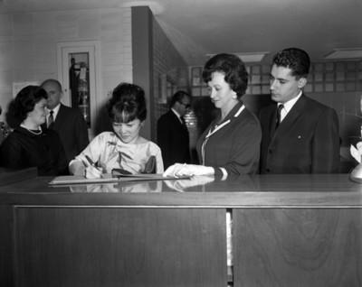 Eva Sámano observa firmar libro a mujer durante visita al INPI
