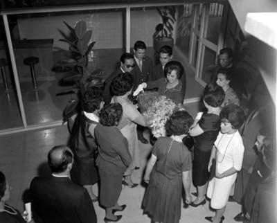 Mujer entrega ramo de flores a Eva Sámano al retirarse de una ceremonia
