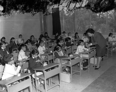 Maestra realiza manualidad durante clases en el salón de una escuela