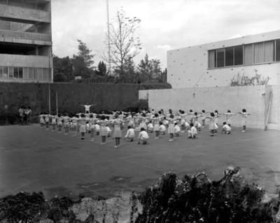 Niños durante clase de educación fisica en el patio de una escuela