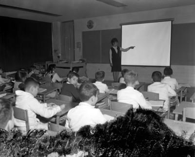 Alumnos observan a maestra durante una clase en un salón