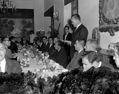 Empreario lee documento durante banquete en un salón