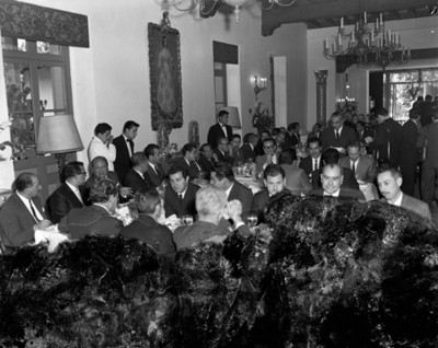 Empresarios conversan durante banquete en un salón