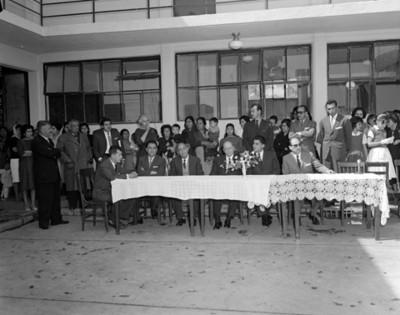Gente sentado y de pie junto a un salón