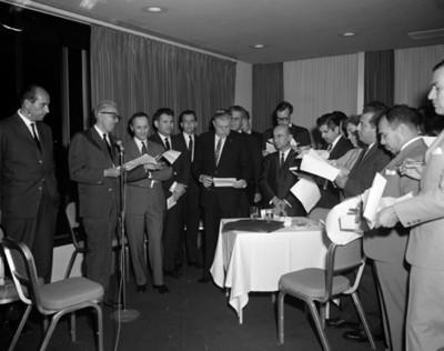 Hombre pronuncia discurso en una conferencia Dina