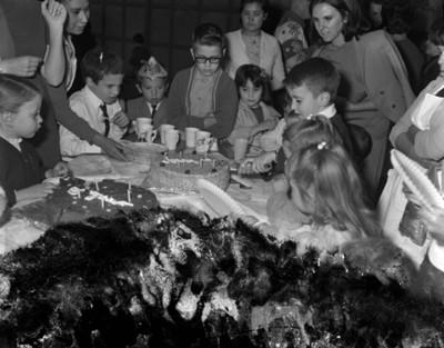 Niño parte pastel durante cumpleaños