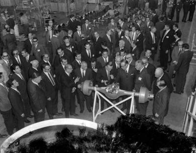 Octaviano Campos Salas y empresarios observan eje de automóvil en la industria manufacturera EATON