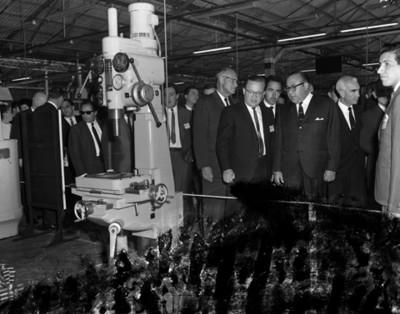 Octaviano Campos Salas y empresarios observan máquina en la fábrica EATON