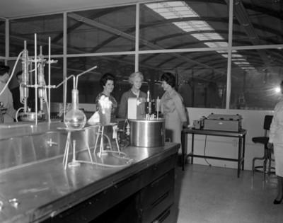 Eva Sámano de López Mateos y mujeres en un laboratorios de la empacadora de alimentos del INPI