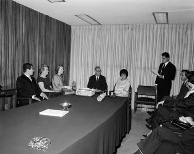 Eva Sámano de López Mateos escucha a un hombre pronunciar discurso durante una ceremonia