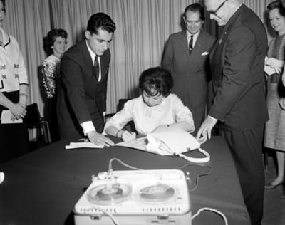 Eva Sámano de López Mateos firma un documento