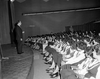 Hombre pronuncia discurso a mujeres durante una conferencia en un auditorio