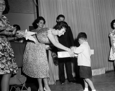 Va Sámano de López Mateos entrega regalo a niño del INPI durante una ceremonia