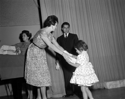 Eva Sámano de López Mateos entrega regalo a un niño del INPI durante una ceremonia