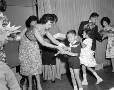 Eva Sámano de López Mateos entrega juguete a un niño del INPI durante una ceremonia