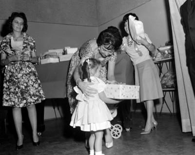 Niño recibe obsequio junto a una mesa