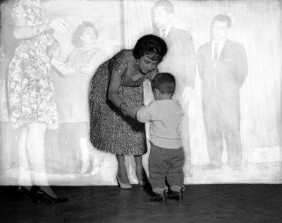 Niño se sostiene de las manos de una mujer