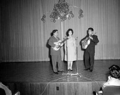 Mujer en medio de dos hombres con guitarra durante una ceremonia