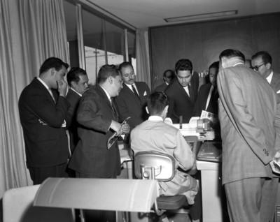 Hombres observan a empleado escribir en máquina