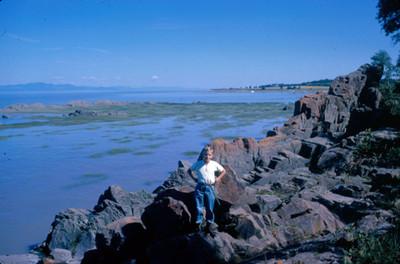 Niño sobre rocas junto al mar